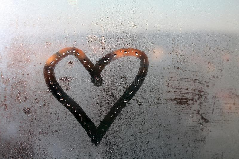 Heart painted on the wet window glass stock photos