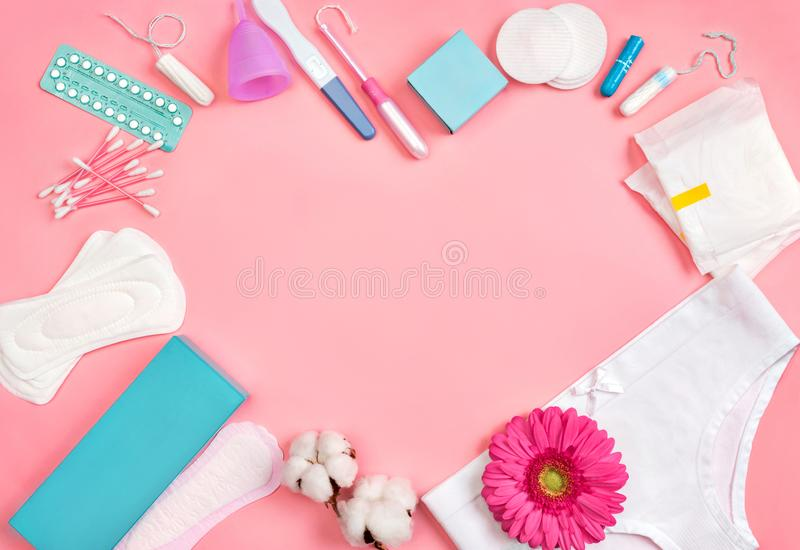 Heart symbol. Sanitary napkins and other hygiene accessories on pink background. Concept of critical days, menstruation stock image