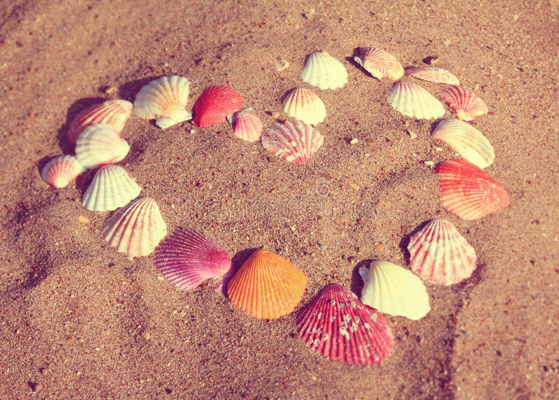Heart symbol from shells on sand - vintage retro style. Heart symbol from sea shells on sand - vintage retro style royalty free stock photography