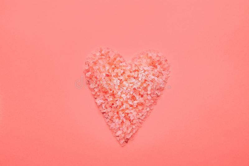 Heart symbol in trendy living coral color made from pink Himalaya salt crystals on monochrome background. Valentine. Mother`s Day Romantic Love Charity Concept royalty free stock photos