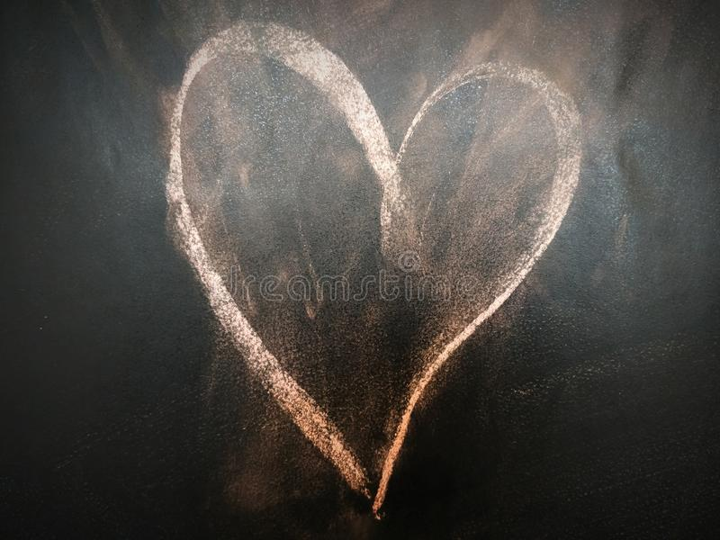 Heart on the blackboard. Heart symbol was drawing on the blackboard. Kids drawing love symbol to the teacher or mother stock photography