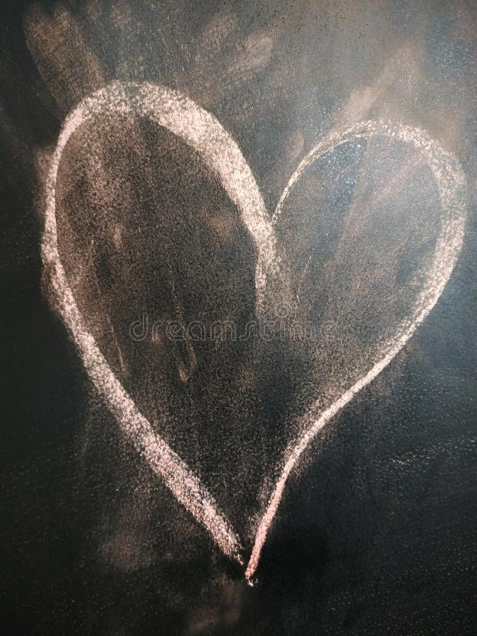 Heart on the blackboard. Heart symbol was drawing on the blackboard. Kids drawing love symbol to the teacher or mother stock images
