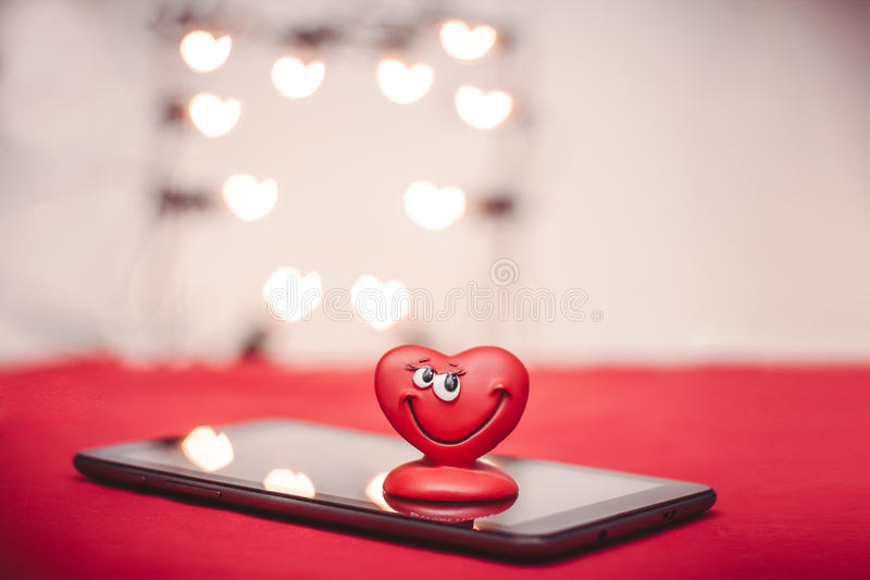 Heart on the tablet PC. Happy red love heart with heart bokeh on the tablet PC Valentines Day background stock images