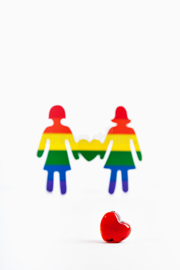Heart and two paper colors of the flag of human homosexuality ar. Red glass heart and two paper colors of the flag of human homosexuality are isolated on a white royalty free stock photos