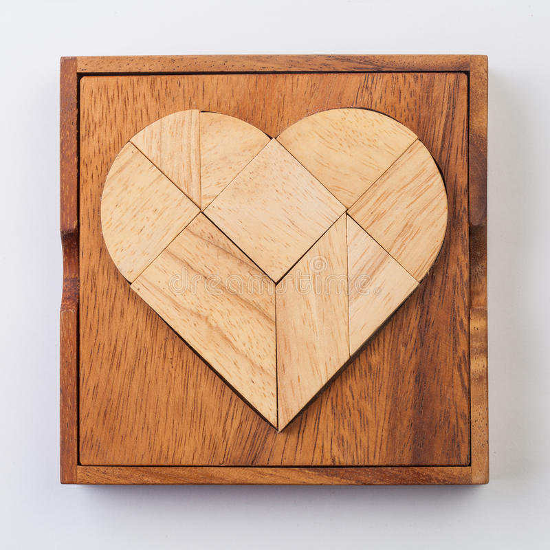 Heart version of tangram, a traditional Chinese Puzzle Game made. Of different wood parts to build abstract figures from them, isolated on white stock photos