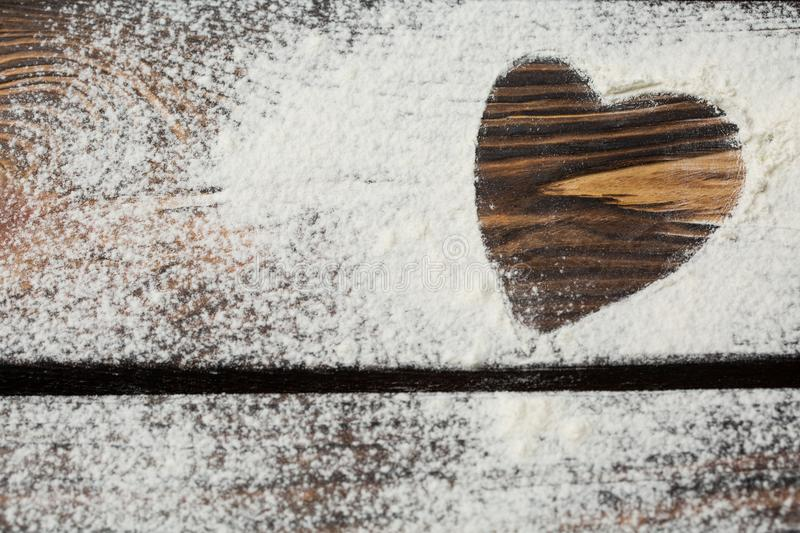 Heart of white flour on a wooden board. Cooking with love. Holiday backing background. Eco food and home cooking. Valentine`s Day royalty free stock photo