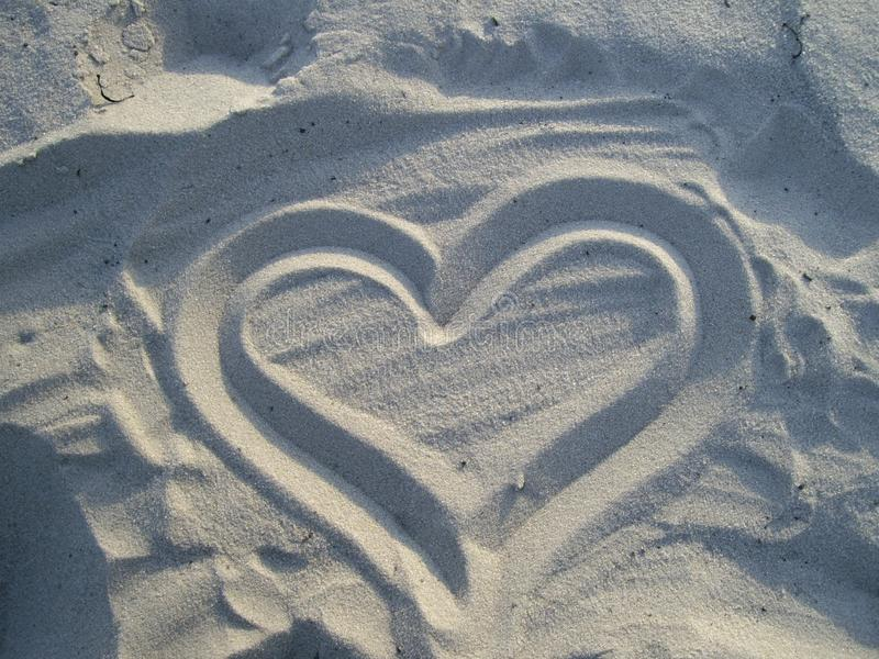Heart on white sand royalty free stock images