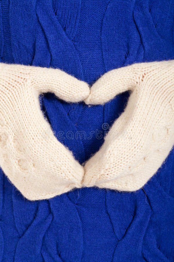 Heart of the winter. White mitten heart on blue sweater isolated on white royalty free stock photos