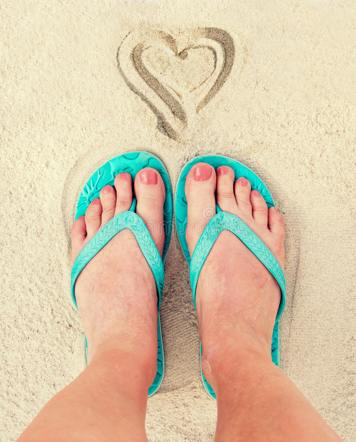 Heart and woman feet wearing flip flops in the sand of a beach. Vintage process royalty free stock photos