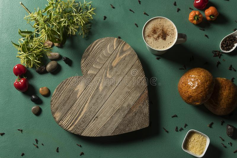 Heart in wood with hot chocolate drink on green background and hard light. With bread and seeds royalty free stock photography