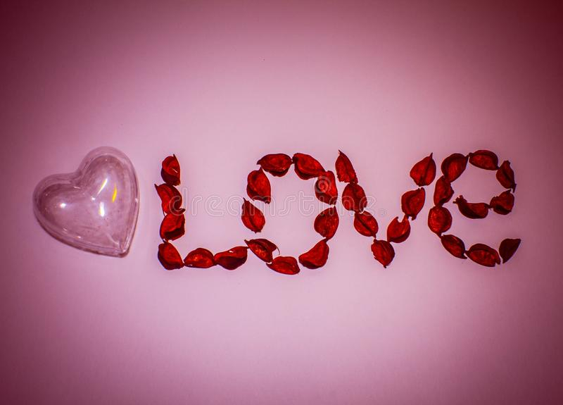 Heart and word love laid out from artificial flowers on a pink background stock photography