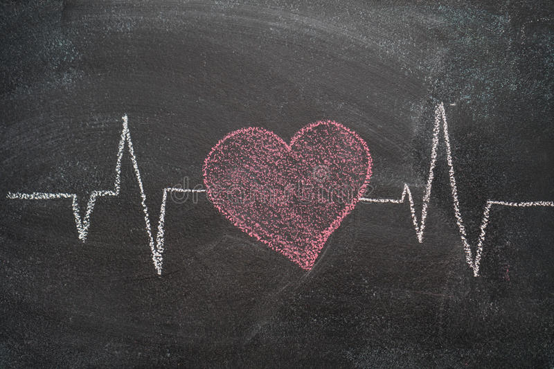 Heartbeat character and design on black chalkboard. Heartbeat character and design drawn with chalk on blackboard royalty free stock photography