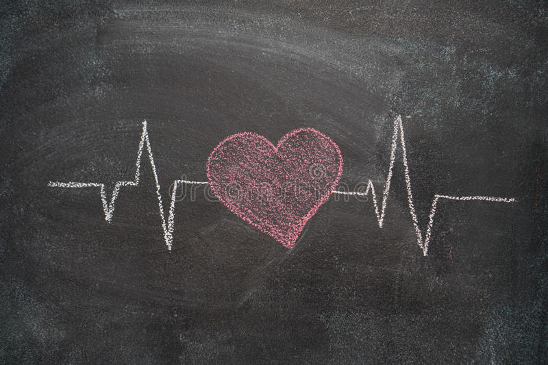 Heartbeat character and design on black chalkboard. Heartbeat character and design drawn with chalk on blackboard royalty free stock photos