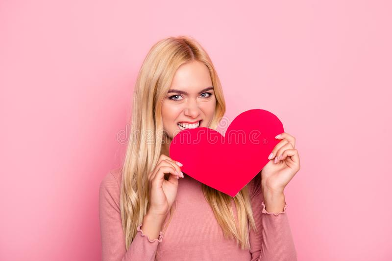She is a heartbreaker! Close up portrait of jealous young attractive woman with long blonde hair. She is holding a heart and royalty free stock image