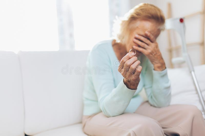 Heartbroken elderly woman holding a wedding ring royalty free stock images