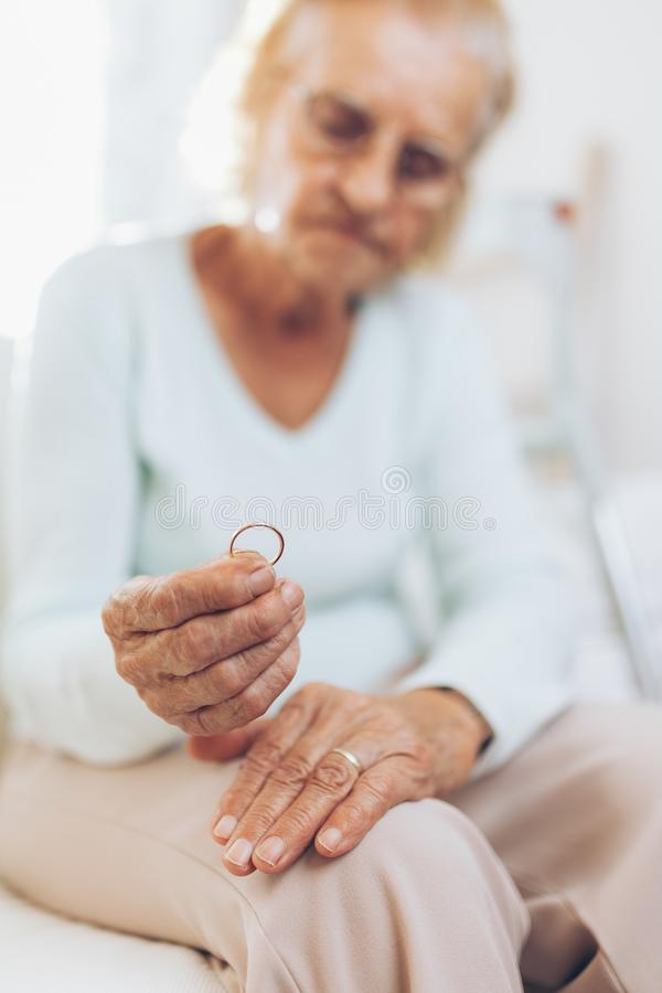 Heartbroken elderly woman holding a wedding ring stock images