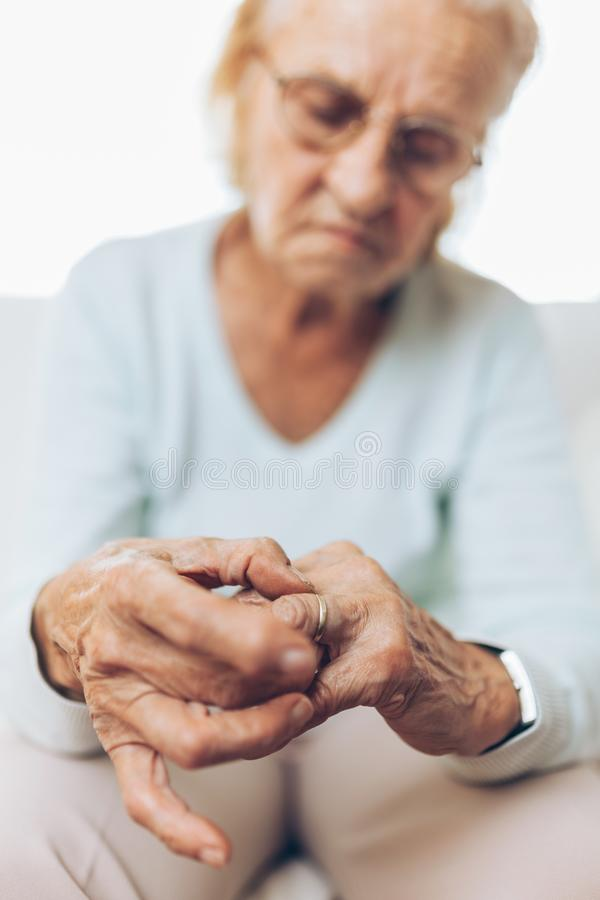 Heartbroken elderly woman holding a wedding ring royalty free stock photo