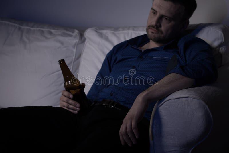 Heartbroken man feeling miserable. And drinking alone stock image
