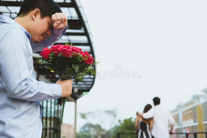 Heartbroken man holding bouquet of red roses feeling sad while s. Asian heartbroken men holding bouquet of red roses feeling sad while seeing women dating with royalty free stock photography