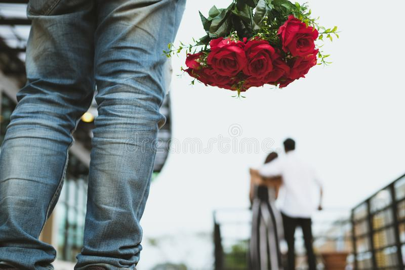 Heartbroken man holding bouquet of red roses feeling sad while s. Asian heartbroken men holding bouquet of red roses feeling sad while seeing women dating with stock photography