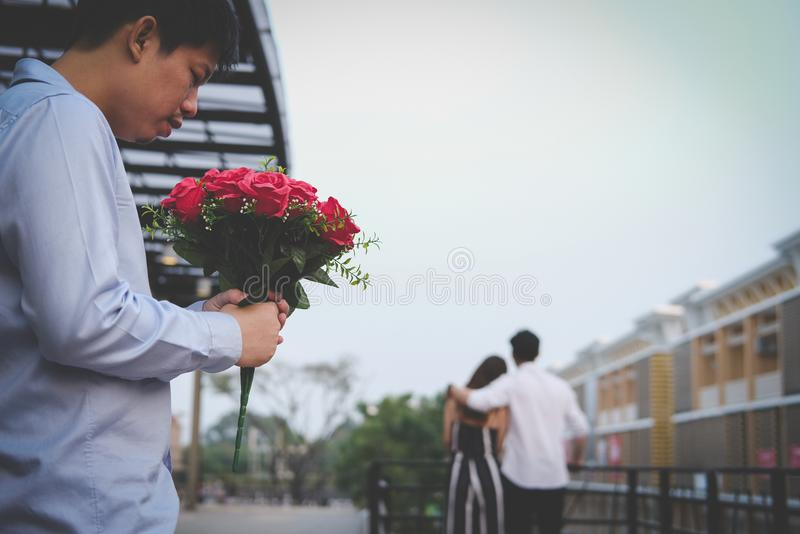 Heartbroken man holding bouquet of red roses feeling sad while s. Asian heartbroken men holding bouquet of red roses feeling sad while seeing women dating with stock image