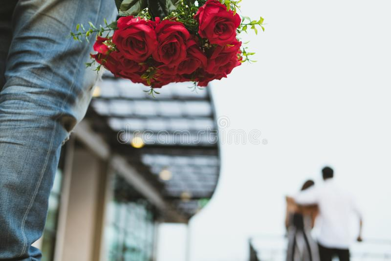 Heartbroken man holding bouquet of red roses feeling sad while s. Asian heartbroken men holding bouquet of red roses feeling sad while seeing women dating with royalty free stock photo
