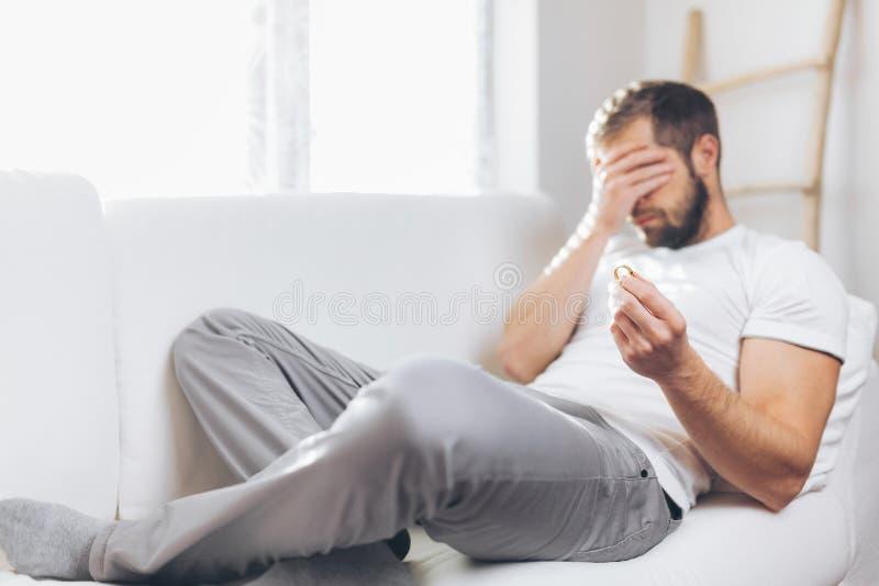Heartbroken man holding a wedding ring. Heartbroken man at home holding a wedding ring stock images