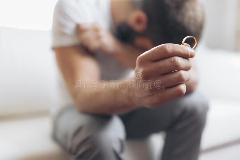 Heartbroken man holding a wedding ring. Heartbroken man at home holding a wedding ring stock photos