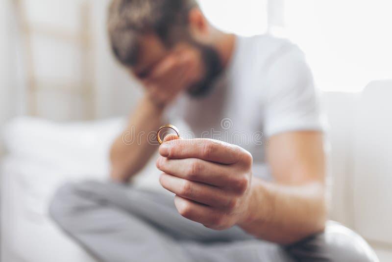 Heartbroken man holding a wedding ring. Heartbroken man at home holding a wedding ring stock photography