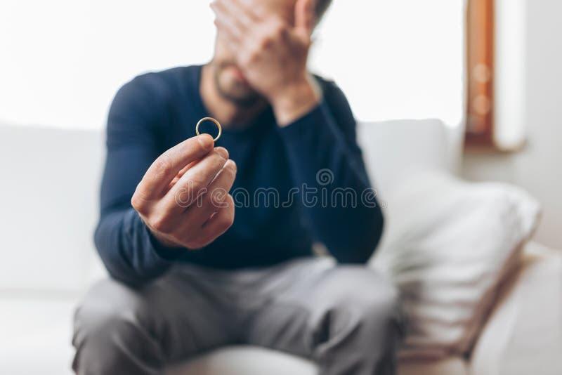 Heartbroken man holding a wedding ring. Heartbroken man at home holding a wedding ring stock image