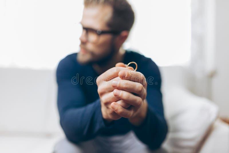 Heartbroken man holding a wedding ring. Heartbroken man at home holding a wedding ring royalty free stock image