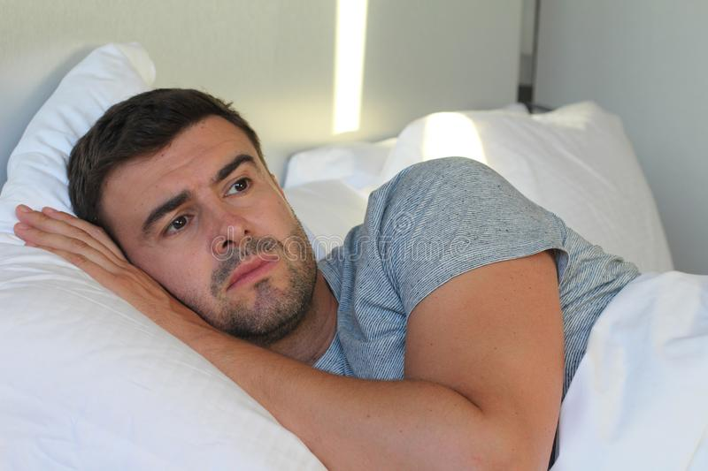 Heartbroken man laying down in bed.  royalty free stock photo