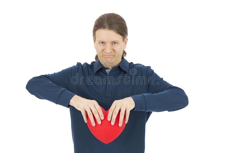 Heartbroken valentines day man looking angry. Angry and frustrated man tearing the heart apart, isolated on white background. Love and valentines day concept royalty free stock photography
