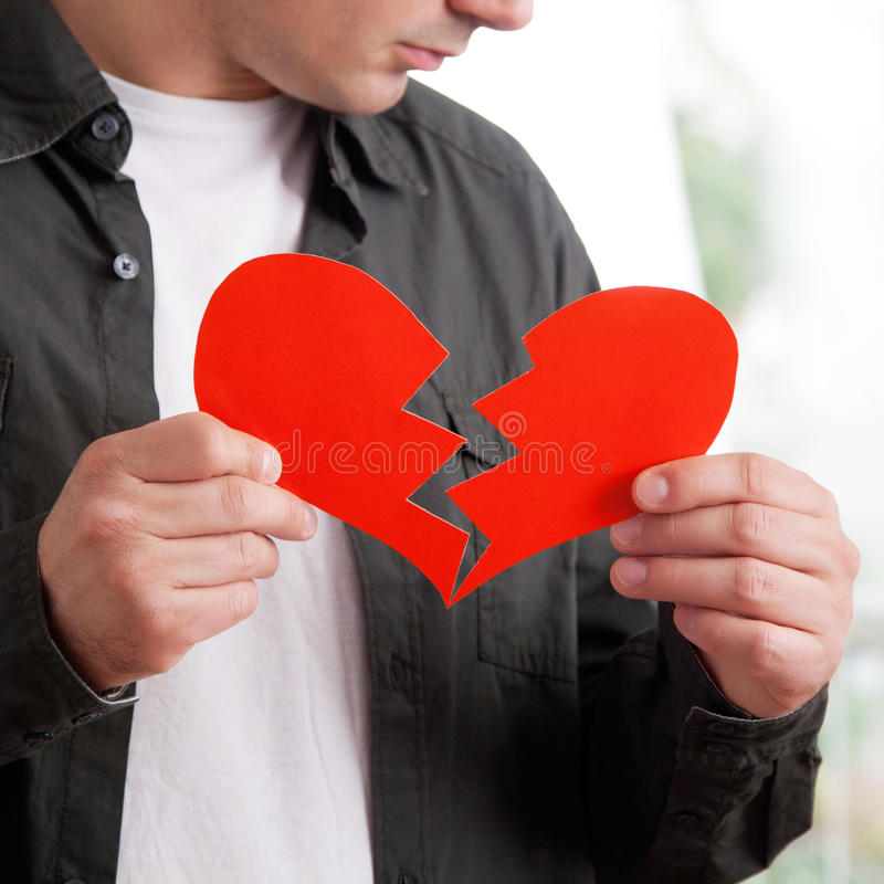 Heartbroken young man. Young man holding ripped heart shaped paper, close up stock photos