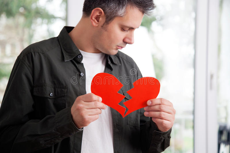 Heartbroken young man. Sad young man holding ripped heart shaped paper stock image