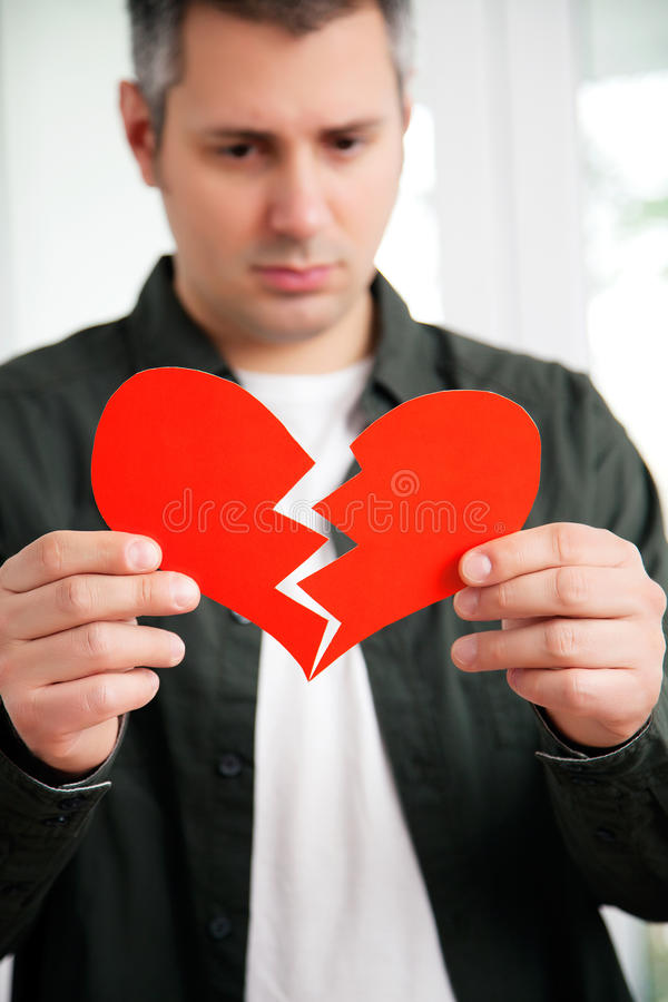 Heartbroken young man. Sad young man holding ripped heart shaped paper, shallow depth of field stock photo