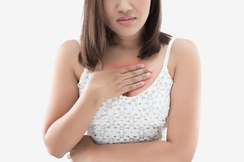 A woman suffering from heartburn on a gray background. Heartburn is a feeling of burning in people chest, and is a symptom of Acid reflux or GERD. A woman royalty free stock photo