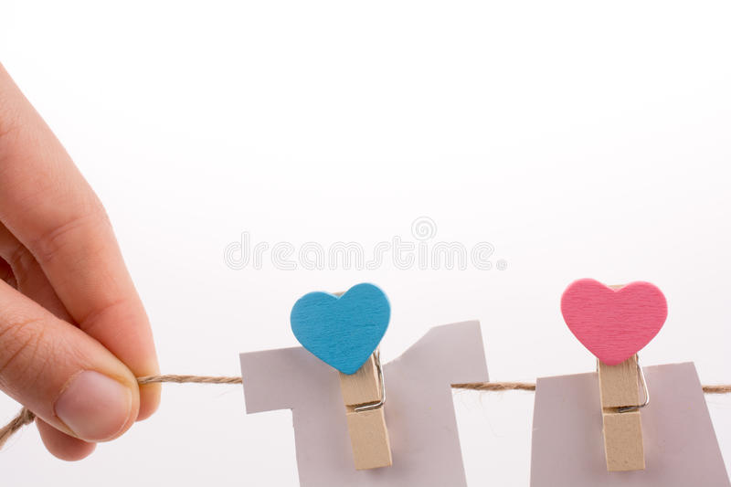Hearted clothespins hanging. On a thin rope stock photos