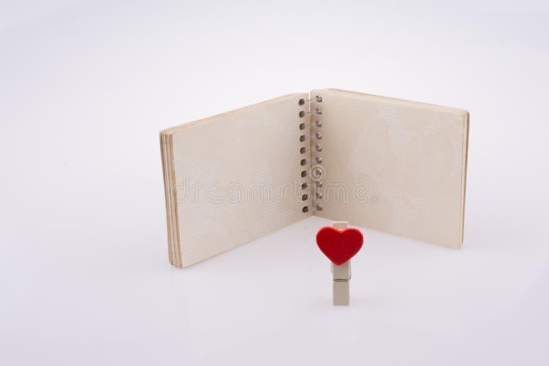 Hearted klem met een notitieboekje stock fotografie