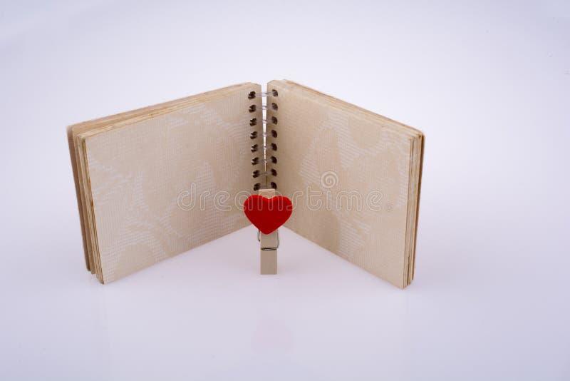 Hearted klem met een notitieboekje stock afbeelding