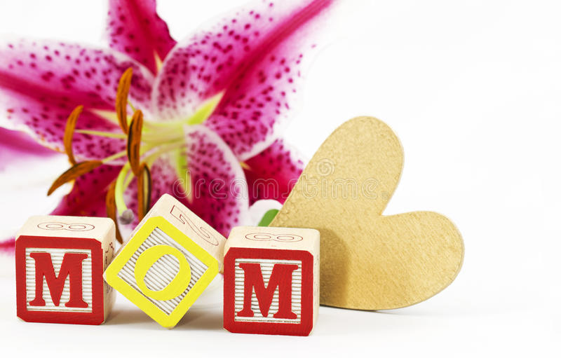 Heartfelt Feelings for Mom. Gold heart and alphabet block letters spelling MOM are placed in front of a single, lily blossom against a white background royalty free stock photo