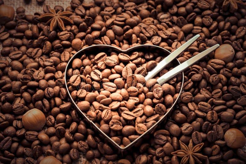 hearting的 咖啡豆和胡说的背景与金属心脏在中部-顶视图塑造 免版税库存图片