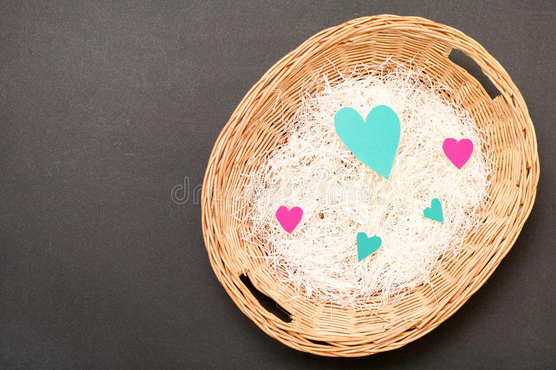 Hearts basket. Real cut out of paper hearts in a wicker basket for your romantic or healthcare concepts - copy space to the left royalty free stock photography