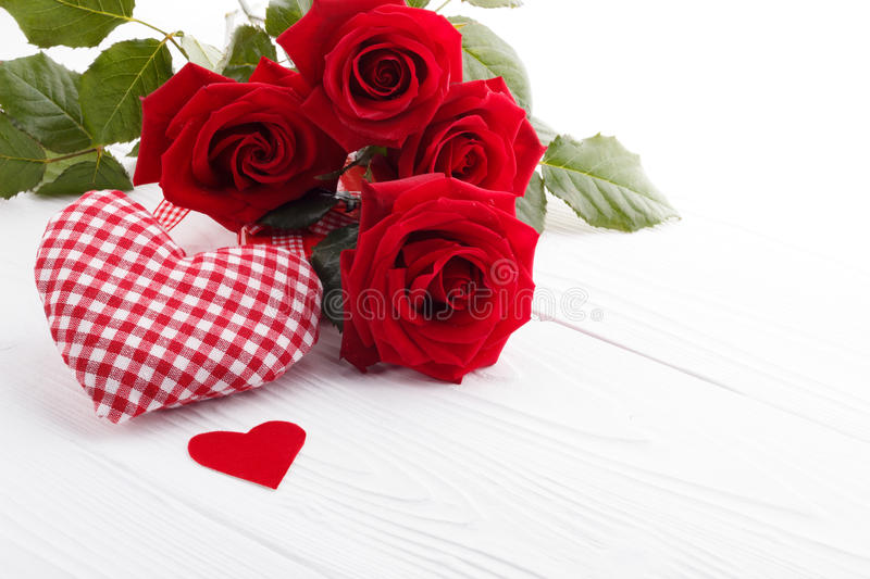 Hearts and a bouquet of red roses on wooden board, stock photography