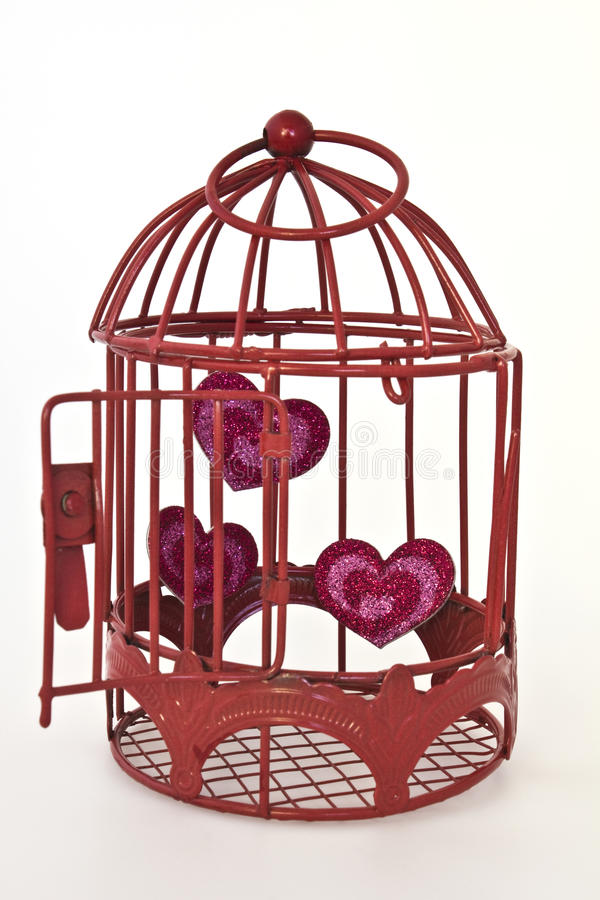 Hearts in a cage. Red glitter hearts in a red cage with the door open to set the hearts free and isolated on a white background royalty free stock image