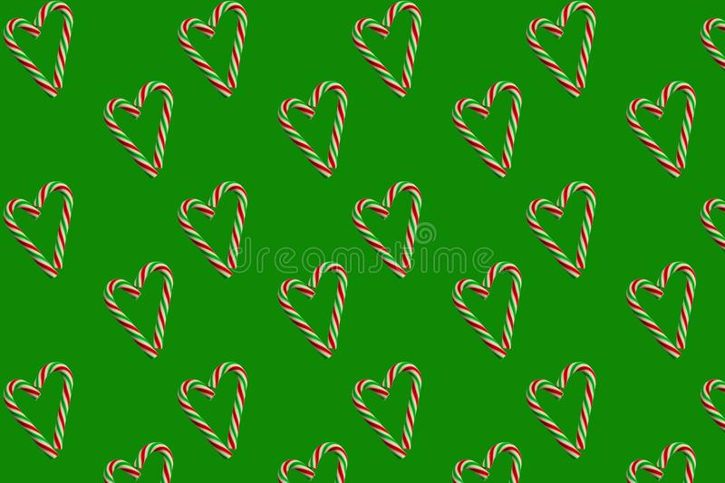 Little hearts from christmas candies on a green background. Seamless wrapping paper concept, wallpaper, pattern for fabric. royalty free stock photography