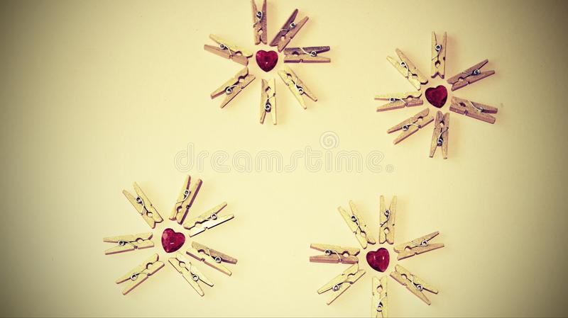 Hearts and clothespins. Today, most pegs are created very cheaply: two locking plastic or wooden prongs are created, which are often caught with a small spring stock image
