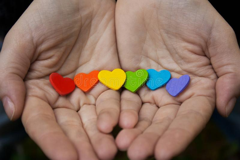 Hearts of the color of the rainbow in women`s hands. The LGBT S stock image