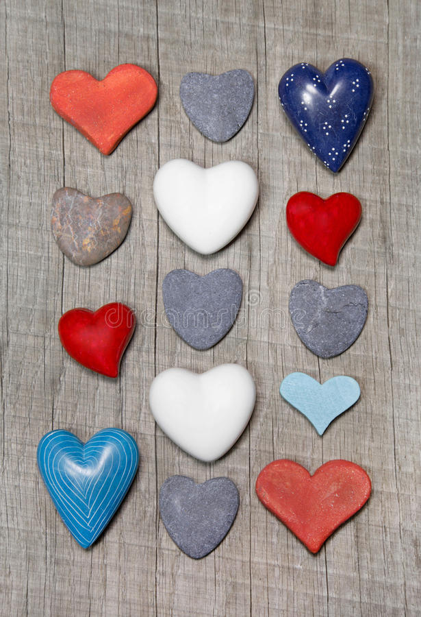Hearts in different colors on wooden background. stock image