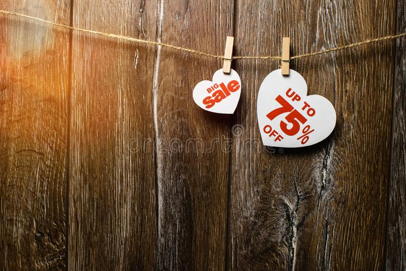 Hearts and discounts with romantic pattern on wooden background. Big sale on one heart and seventy-five percent. On another hanging on rope by clothespins stock images